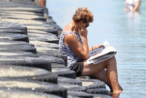 Napier woman Jan Cooper enjoyed reading the newspaper while keeping her feet cool in Pandora Pond yesterday. Photo / Duncan Brown