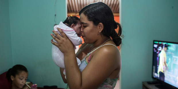 Cleane Serpa, 18, holds her month-old cousin, Maria Eduarda, who was born with microcephaly, in Recife, Brazil, last week. Photo / Lianne Milton / The Washington Post