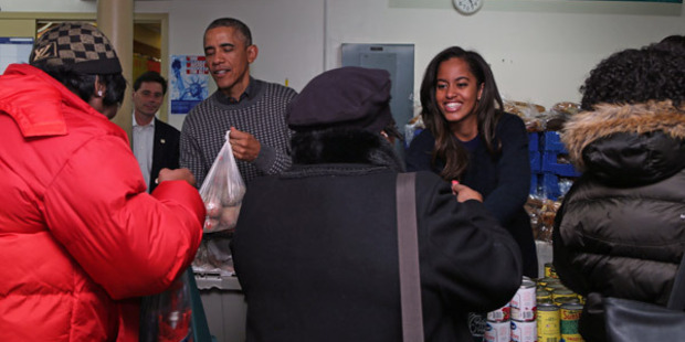 Obama and daughter, Malia, hand out Thanksgiving food to the needy. Photo / Getty Images