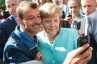 UNDER PRESSURE: German Chancellor Angela Merkel (right) has pictures taken with refugees in Berlin, Germany, in September. Her migrant troubles have reignited in the new year, with an outcry over assaults in Cologne blamed largely on foreigners, and Bavarian allies pushing for a cap on asylum-seekers.PHOTO/AP