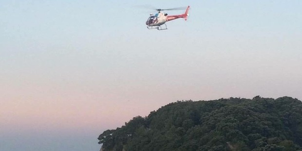 A rescue chopper searching for the teen boy after he was swept from the rocks at Mt Maunganui. Photo / Lauren Hines