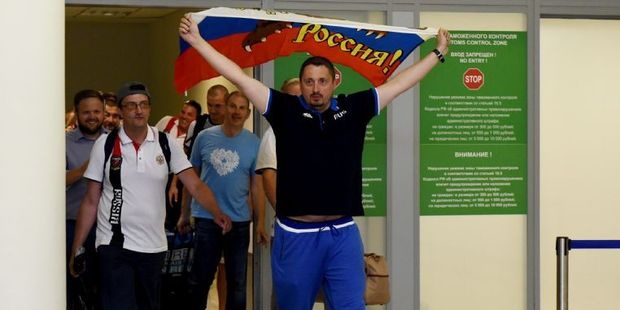 Russia's football fans leader Alexander Shprygin holding a flag as he leaves with other fans the international Sheremetevo airport near Moscow after being expelled from France. Photo / AFP