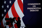 A cameraman is silhouetted against an an American flag during preparations for the presidential debate at Hofstra University in New York. Photo / AP