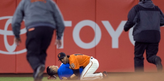Angel Pagan holds down a man who ran onto the field during the fourth inning of the Giants' baseball game against the Los Angeles Dodgers. Photo / AP