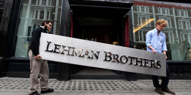 Two employees of Christie's auction house maneuver the Lehman Brothers corporate logo which was up for sale. Photo / Getty