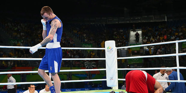 Steven Donnelly of Ireland looks dejected as Mohammed Rabii of Morocco kisses the canvas in victory. Photo / Getty Images