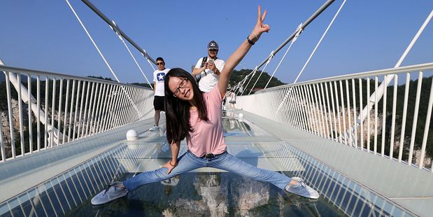 A tourist poses for a photograph on the record breaking bridge. Photo / Getty Images
