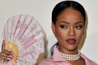 Rihanna poses with a pastel pink oriental fan featuring the