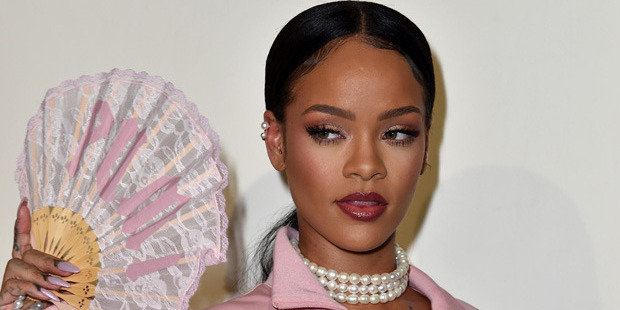 """Rihanna poses with a pastel pink oriental fan featuring the """"Puma"""" logo. Photo / Getty"""