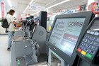 Instructions are displayed on the screen of a self checkout counter in a Coles supermarket. Photo / Bloomberg