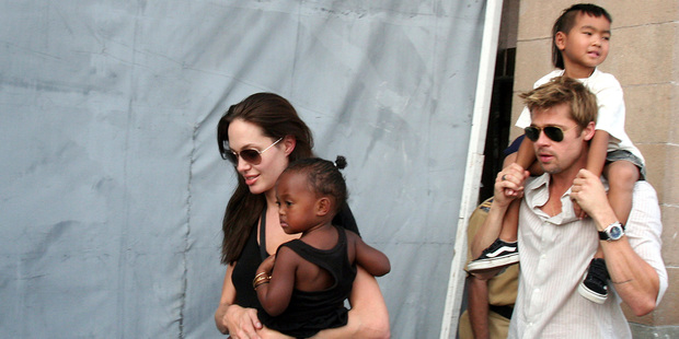 Angelina Jolie with daughter Zahara, and Brad Pitt with Maddox in 2006. Photo / AP