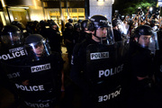 Police officers in riot gear stand by as protesters gather in Charlotte, N.C. on Thursday, Sept. 22, 2016. The curfew has ended for Friday in Charlotte following a night of mostly peaceful protests o