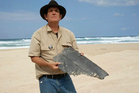 Blaine Gibson holding a piece of aircraft debris on a beach in Madagascar. Gibson is the first person searching for the plane who's actually found any trace of it. Photo / AP
