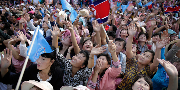 North Korean men and women wave flags and cheer as they watch a military parachuting demonstration. Photo / AP