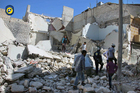 A Civil Defence group and residents inspect damaged buildings after airstrikes hit the Bustan al-Qasr neighborhood in Aleppo, Syria. Photo / AP