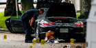A police officer investigates a car belonging the lawyer who shot and injured multiple people before he was killed by police in Houston. Photo / AP
