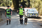 NO SIGN: Sergeant Craig Burrows (Kamo) Constable Tony Harris (Auckland) and cadaver dog Phoenix were part of an unsuccessful search for Kimble Moore's body off Duncan Road in March. PHOTO/PETER DE GRAAF