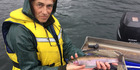 TROUT: Fish and Game officer Mark Sherburn holds a green tag trout before releasing it. PHOTO/SUPPLIED