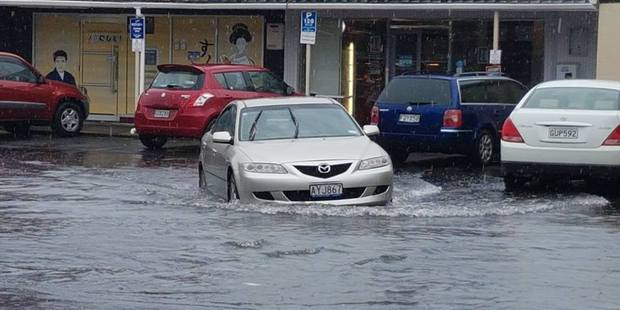 Cars make their way through flooding in Browns Bay, Auckland. Photo / Facebook