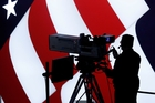 A cameraman is silhouetted against an an American flag during preparations for the presidential debate at Hofstra University. Photo / AP