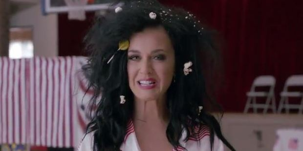 In the clip, Katy Perry is seen waking from her slumber sporting patriotic pajamas and messy bed hair, complete with popcorn and a lollipop as she declares. Photo / Funny or Die