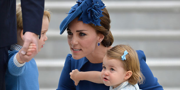Kate, while holding Charlotte, squats down to Prince George's height in order to speak to her son. Photo / Getty