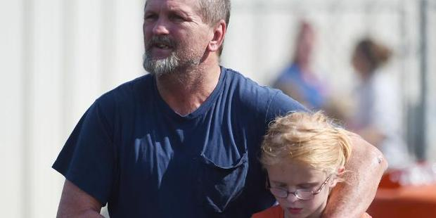 Joey Taylor walks with his daughter Josie Taylor after the shooting. Photo / AP