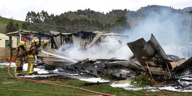 The rural fire service dampen down the remains of a house fire at Raurimu. Photo / John Chapman