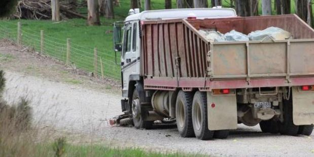 A motorcycle lies on the road in front a a truck following a collision near Wallacetown this morning. Photo: Allison Beckham / Otago Daily Times