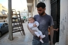 Syrian Yehya Maatouq holds his four-month-old daughter Wahida. Photo/AFP