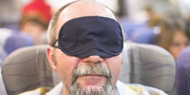 Make sure you grab that eye mask that the airline hands you. Photo / 123RF