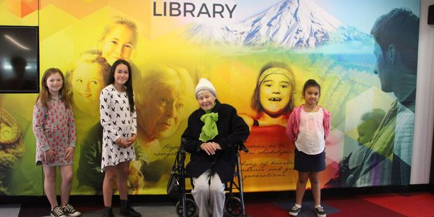 (l-r) Alex Petrie, Adelaide Petrie, Gwelfa Burgess and Coco Tihema stand by their images on the light box at Stratford Library.