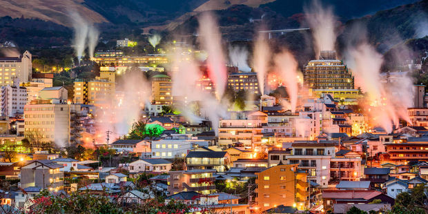 Steam rises from Beppu's hot spring bath houses. Photo / 123RF