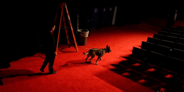 An officer walks his dog through the debate hall at Longwood University during preparations for the vice-presidential debate in Virginia. Photo / AP