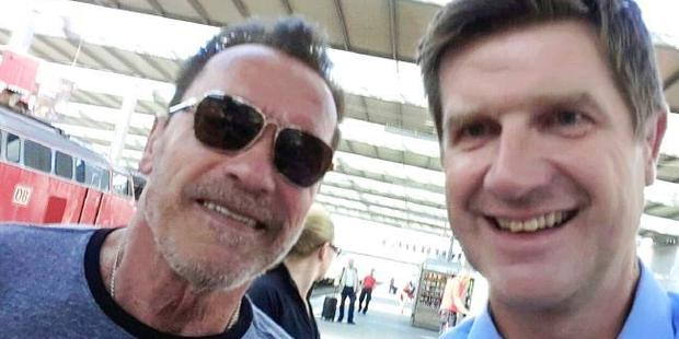 Former Californian state governor Arnold Schwarzenegger poses with police officer Stefan Schmitt for a selfie in the main train station in Munich, Germany. Photo / AP