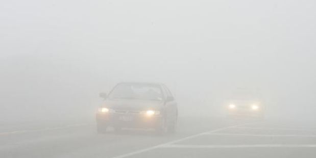 Cars travel through thick fog at the top of the Northern Motorway. Photo / Supplied