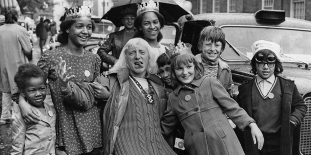 English DJ and television presenter Jimmy Savile joins a group of under-privileged and disabled children on a day out to Southend. Photo / Getty