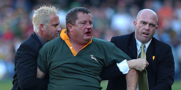 Loading Springbok supporter Pieter Van Zyl is removed from the field by officials after assaulting Irish referee David McHugh. Photo / Getty Images