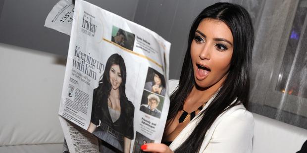 Kim Kardashian reads a Louisville Courier Journal newspaper featuring herself in 2009. Photo / Getty
