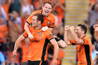 Luke DeVere of the Roar is congratulated by team mate Corey Brown after scoring a goal during the round one A-League match. Photo / Getty Images.