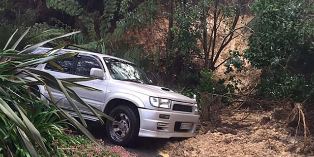 A car sits next to a slip that crashed though a woman's house on Riverview Rd. Photo / Supplied