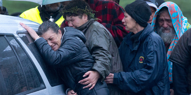 Friends and family mourn as the bodies of two people murdered in the tiny settlement of Kinohaku. Photo / Alan Gibson