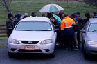 Friends and family mourn as the bodies of two people killed in the tiny settlement of Kinohaku, near Kawhia. Photo / Alan Gibson