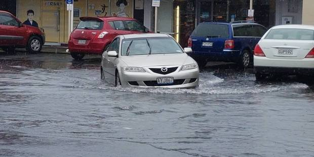 Loading Cars drive through flooding in Brown's Bay, Auckland earlier this week.