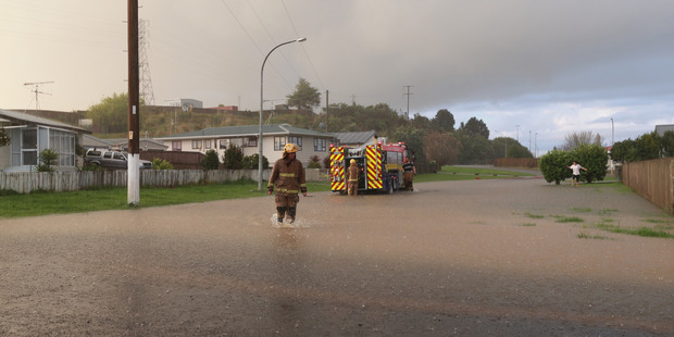 Loading A fireman wades through water as Mary Road in Huntly is flooded after heavy rains across the Waikato region. Photo / Doug Sherring