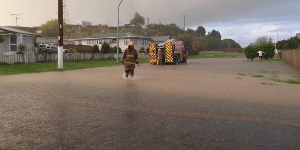A fireman wades through water as Mary Road in Huntly is flooded. Photo / Doug Sherring