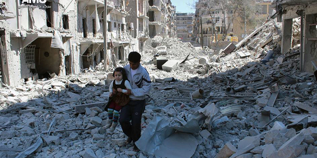 A Syrian man holding a girl as he stands on the rubble of houses that were destroyed by Syrian government forces air strikes in Aleppo. Photo / AP