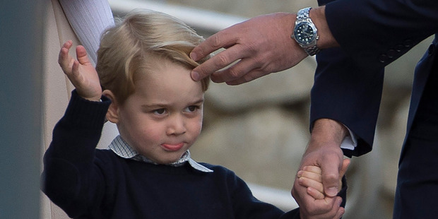 Britain's Prince William, the Duke of Cambridge, fixes Prince George's hair as he waves to the crowd. Photo / AP