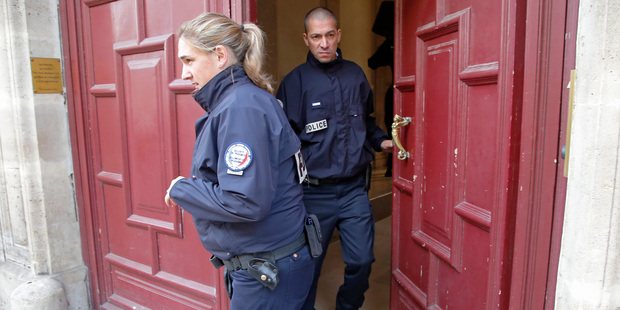 French police officers exit the Paris apartment. Photo / AP