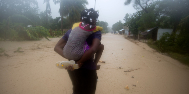 A woman and a child walk in a waterlogged street as they head to a shelter under the pouring rain caused by Hurricane Matthew, in Leogane, Haiti. Photo / AP